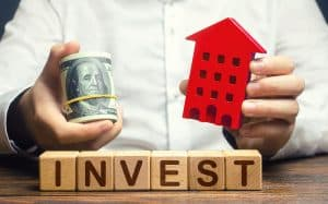 A Man With Dollars And A House Figurine And The Word Invest.