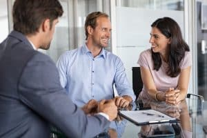 Mature smiling couple meeting financial advisor for investment at office