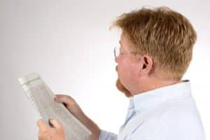 Mature male reads the stock market
