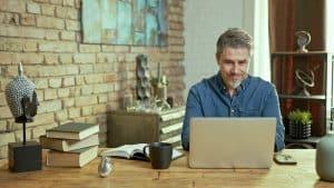 Older man tele working with laptop