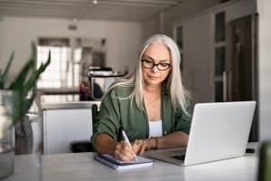 Senior stylish woman taking notes in notebook